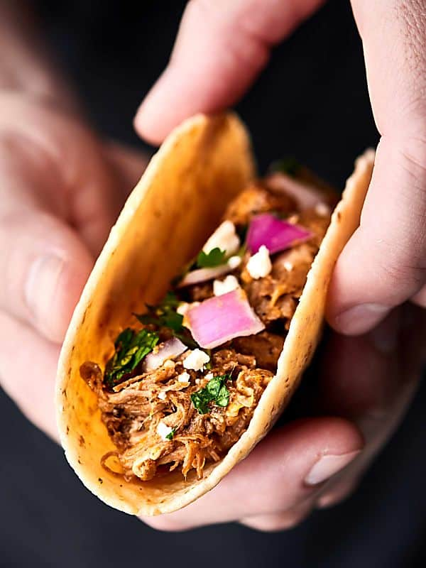 carnitas taco held