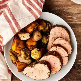 This Pork Tenderloin Recipe is quick, easy, healthy, and so tasty! Loaded with pork, sweet potatoes, brussels sprouts, onion, and apples, and smothered in balsamic vinegar and spices: garlic, rosemary, thyme, paprika, salt, and pepper! showmetheyummy.com #sheetpandinner #porktenderloin