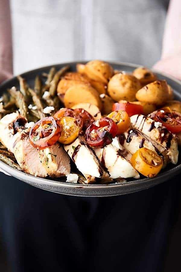 This Bruschetta Chicken Recipe is a quick, easy, light, healthy, packed with flavor summer sheet pan wonder! Only ONE pan required and loaded with tender chicken, green beans (or asparagus), and potatoes and gets topped with the easiest bruschetta recipe! showmetheyummy.com #sheetpandinner #healthy #bruschetta #chicken