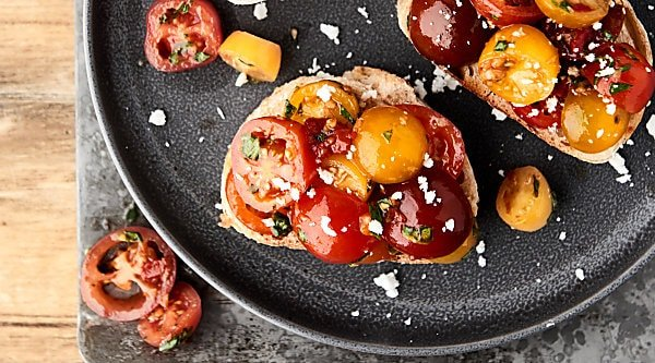 This easy bruschetta recipe is a healthy summer classic! Juicy tomatoes tossed with sun dried tomatoes, garlic, a touch of oil, balsamic vinegar, and fresh basil . . . we can't get enough of this stuff!showmetheyummy.com #bruschetta #summerrecipe #healthy #vegan