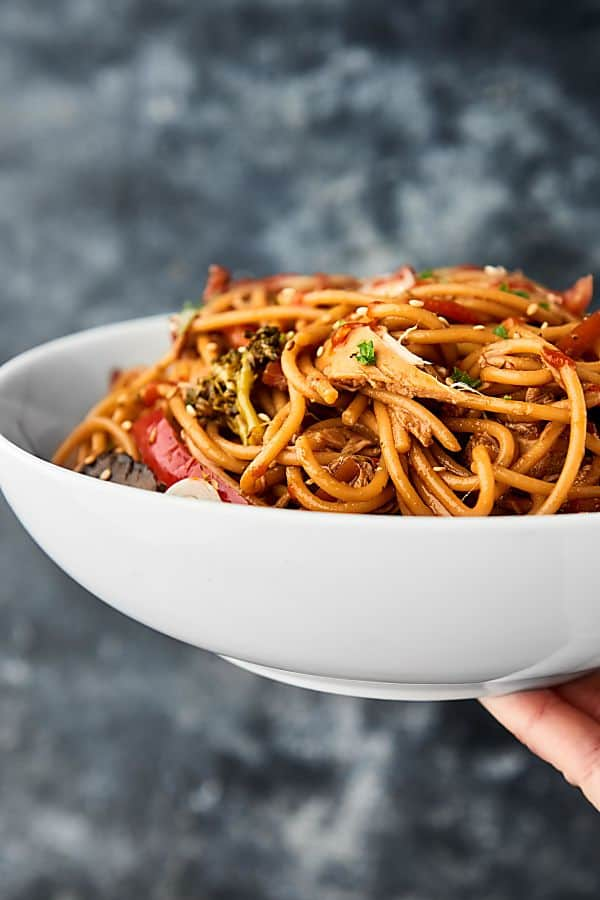 Slow cooker lo mein in a bowl held