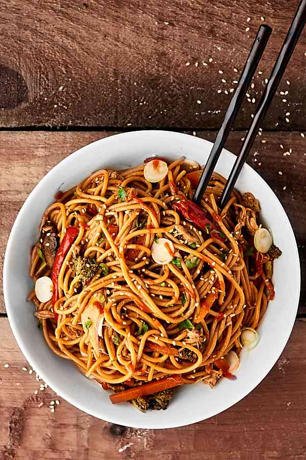 Bowl of lo mein with chopsticks above