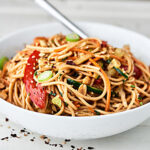 This Asian Pasta Salad Recipe is loaded with a homemade dressing: sesame oil, vinegar, lime juice, honey, soy sauce, spices, etc. - fresh crunchy veggies: carrots, bell pepper, cucumbers - and other great mix-ins: noodles, peanuts, and cilantro! Light, fresh, quick and easy! showmetheyummy.com #pasta #salad #asian #summer #pastasalad