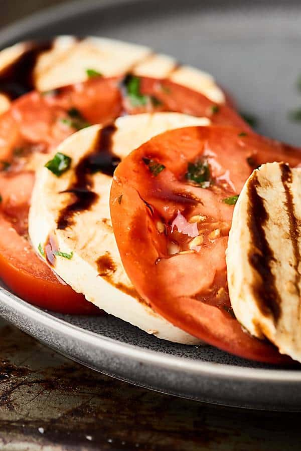 This Easy Caprese Salad is an easy, fresh summer classic! Juicy sliced tomatoes and creamy mozzarella seasoned with extra virgin olive oil, balsamic vinegar, garlic, fresh basil, and salt. Don't forget the extra drizzle of balsamic glaze! showmetheyummy.com #caprese #salad