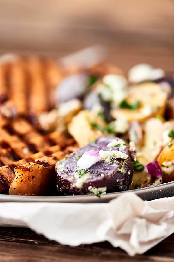 closeup of plate with grilled potatoes and pork chops