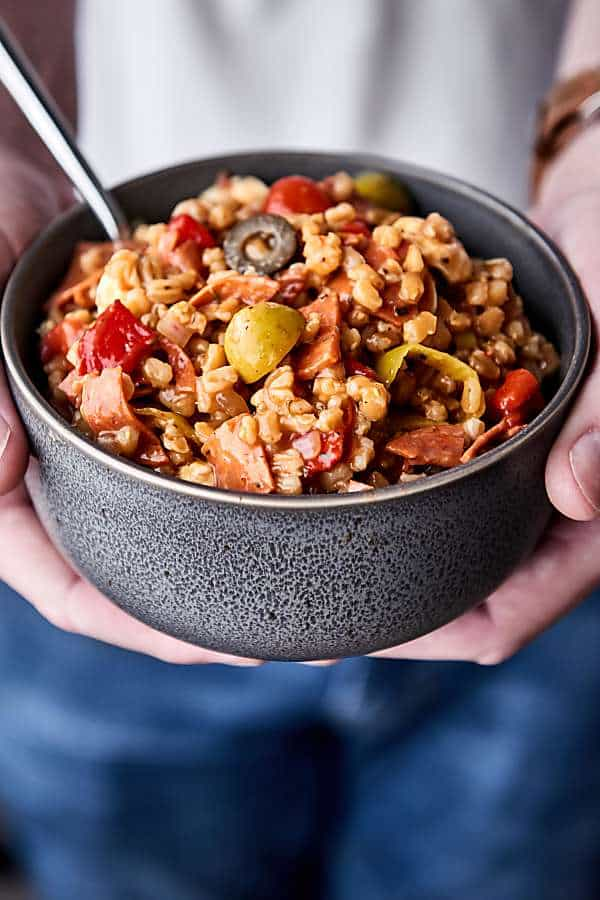 bowl of antiipasto farro salad held two hands