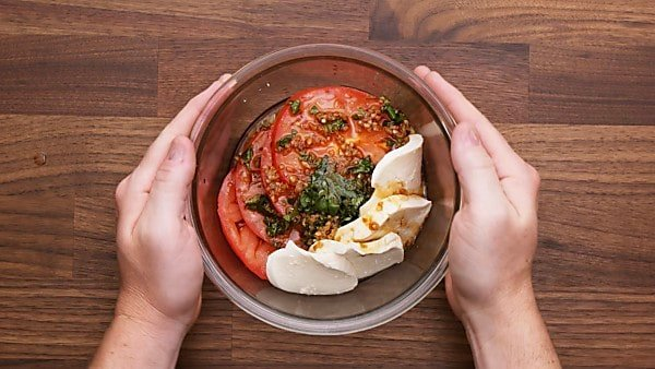 Balsamic glaze and caprese salad ingredients in small bowl to marinate