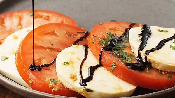 Balsamic glaze being drizzled over caprese salad