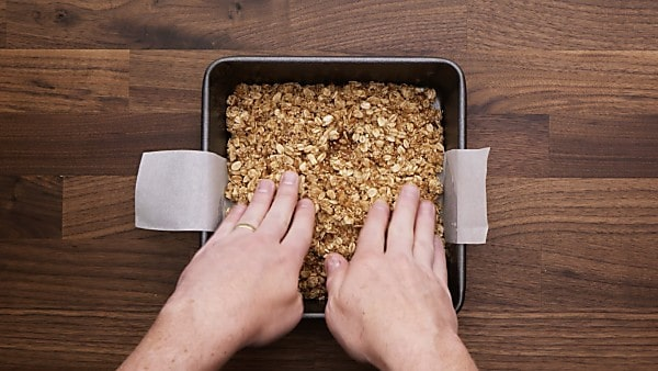 oat crust being pressed into baking pan