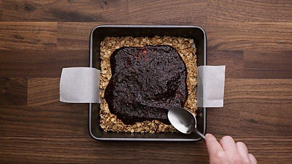 jam being spread over crust