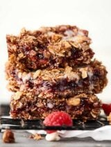 These Vegan Raspberry Oatmeal Bars are SO easy and tasty. This vegan gluten free dessert is loaded with oats, brown sugar, coconut oil, walnuts, and your choice of preserves or jam!showmetheyummy.com #vegan #dessert #oatmealbars #raspberry