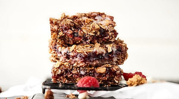 These Vegan Raspberry Oatmeal Bars are SO easy and tasty. This vegan gluten free dessert is loaded with oats, brown sugar, coconut oil, walnuts, and your choice of preserves or jam! showmetheyummy.com #vegan #dessert #oatmealbars #raspberry