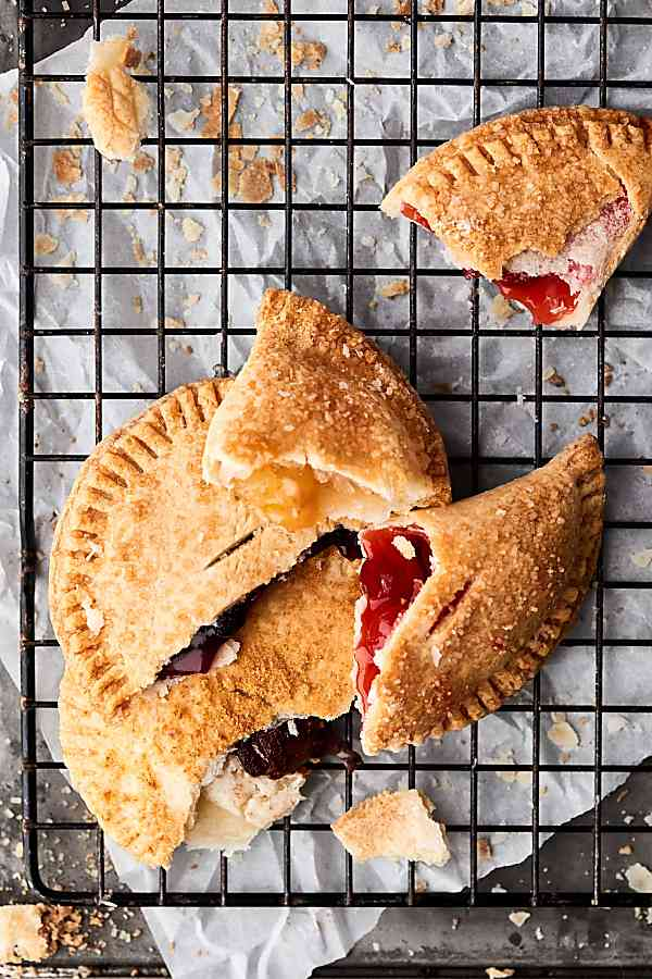 These Air Fryer Hand Pies are SO quick and easy to make. We're making 4 flavors today: S'Mores, Blueberry, Caramel Apple, and Cherry! I used store-bought crust and fillings to make this ULTRA easy, but feel free to make your own homemade crust and fillings! showmetheyummy.com #airfryer #handpies #cherry #smores #blueberry #apple #caramel #nutella