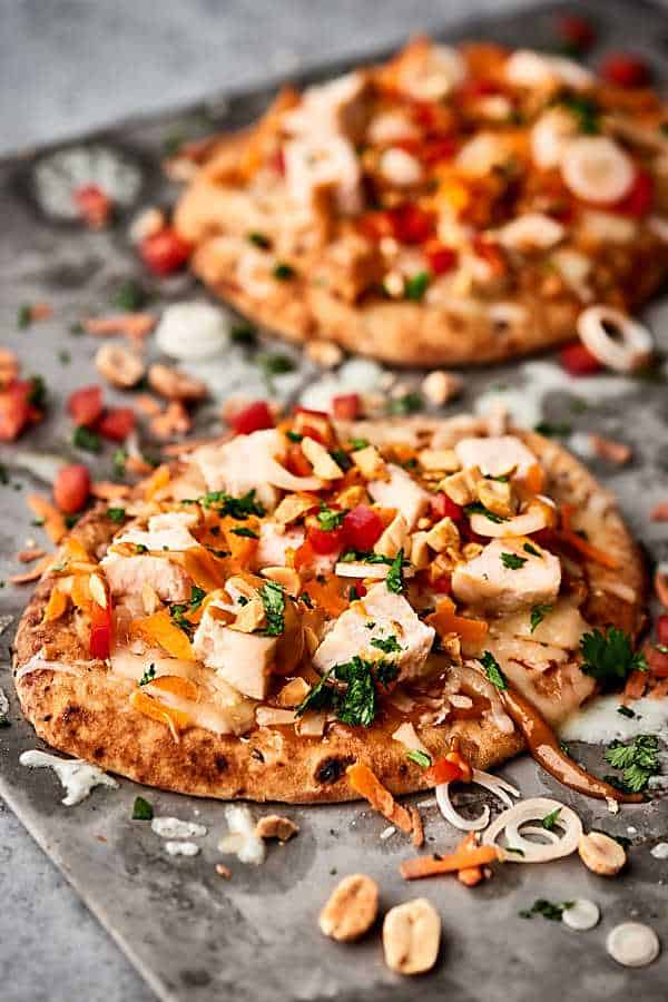 Easy Thai Chicken Naan Pizza Recipe. Store bought naan topped with a homemade easy peanut sauce, monterey jack cheese, chicken, carrots, peppers, cilantro, green onion, and peanuts! SO quick and delicious! showmetheyummy.com #naan #pizza #thai #chicken