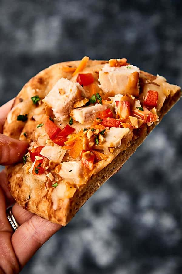 piece of thai chicken naaan pizza held