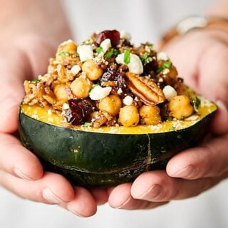 Instant Pot Stuffed Acorn Squash. Squash stuffed with veggies, wild rice, spices, herbs, chickpeas, cranberries, pecans, and more! Perfect for an easy meatless weeknight meal or as a vegetarian/vegan Thanksgiving side or main! Easy, healthy, can be vegan and gluten free! showmetheyummy.com #vegan #thanksgiving #instantpot #stuffedacornsquash #wildrice