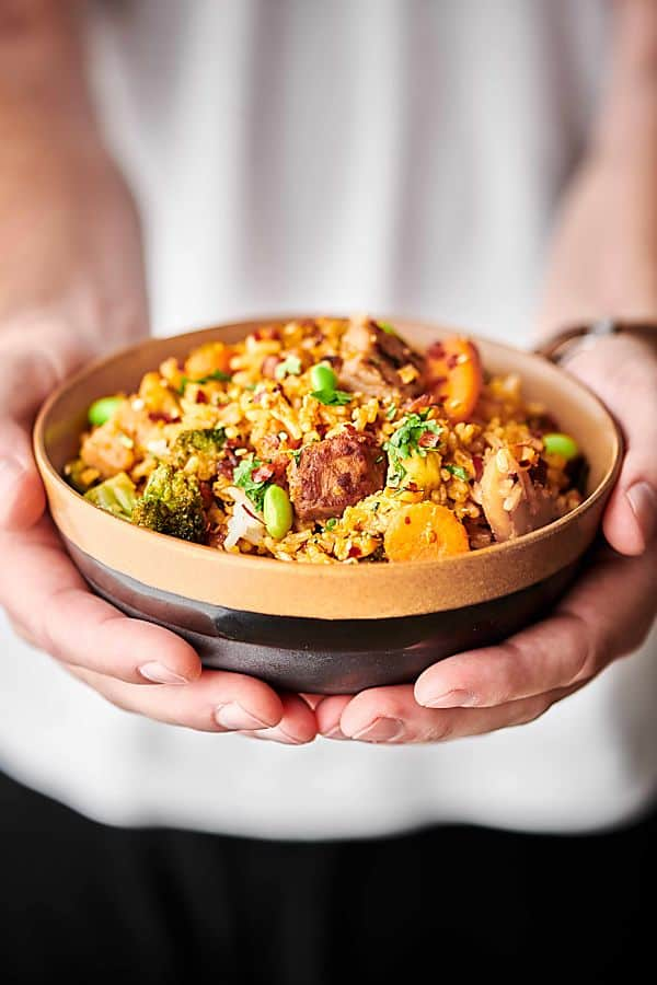 Bowl of fried rice held both hands