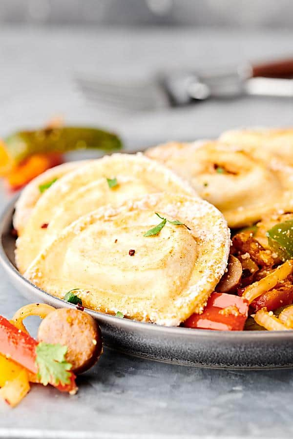 #ad Sheet Pan Pierogies with Sausage and Peppers. Garlic and parmesan pierogies baked until crispy with beer brats, peppers, and onions! A quick and easy family dinner that is sure to be a crowd favorite! showmetheyummy.com Made in partnership w/ @easyhomemeals #sheetpan #dinner #pierogies #sausage #peppers