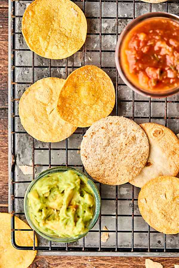Air fryer tortilla chips on cooling rack with guac and salsa above