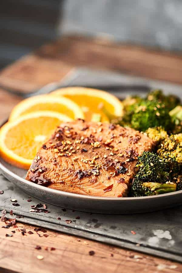 Sheet Pan Asian Salmon and Broccoli. A healthy one pan meal loaded with salmon, broccoli, and an Asian inspired marinade: soy sauce, orange juice, sesame oil, hoisin sauce, garlic powder, ginger, pepper, and crushed red pepper. Only 10 ingredients and 10 minutes of prep! showmetheyummy.com #sheetpan #dinner #healthy #salmon #asian #broccoli