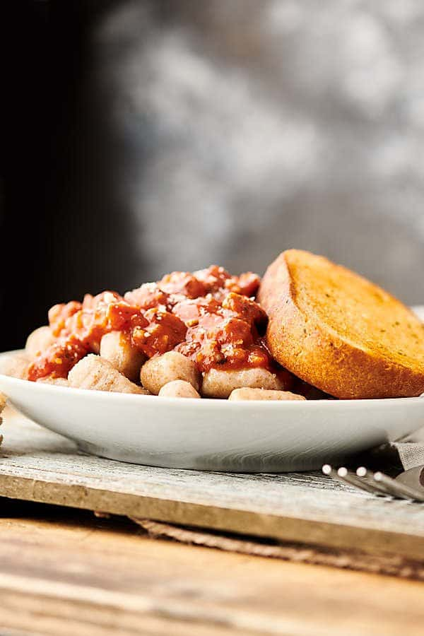 Bolognese on plate with garlic bread