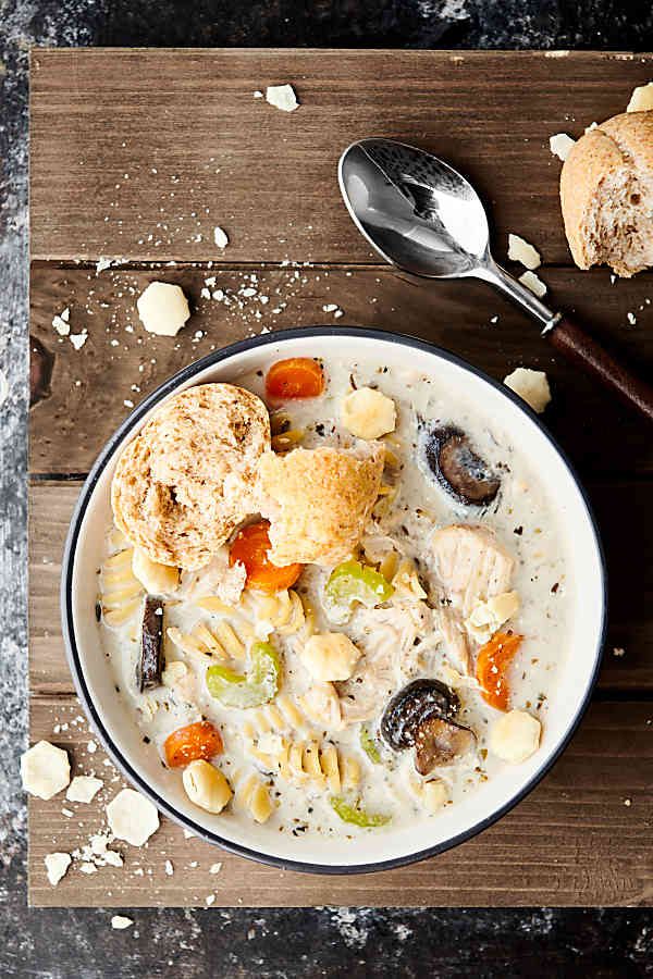This Crockpot Creamy Chicken Noodle Soup Recipe is packed with healthy foods like lean chicken, veggies: onion, garlic, carrots, celery, mushrooms - and spices. It's also SO creamy and satisfying thanks to a bit of half & half, a touch of cream cheese, and rotini pasta noodles. Hearty, but not heavy at all! The perfect cozy winter soup. showmetheyummy.com #crockpot #chickennoodlesoup #chicken #soup #pasta
