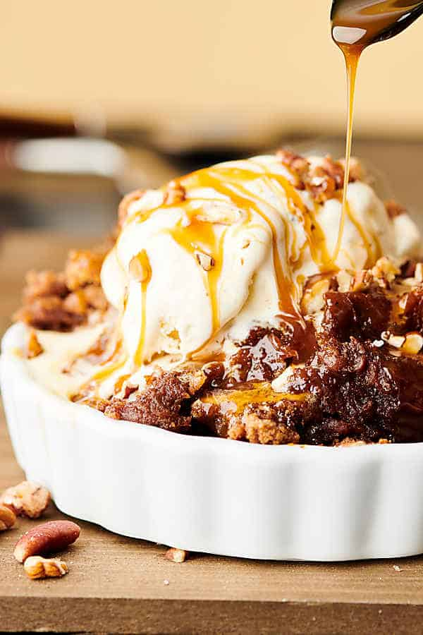 Crockpot Pumpkin Dump Cake. An easy homemade pumpkin pie filling made with pumpkin, brown sugar, vanilla, cinnamon, ginger, cloves, nutmeg, and salt gets topped with caramel, pecans, spice cake mix, and butter. Don't forget to serve it warm with a scoop of vanilla ice cream! showmetheyummy.com #crockpot #pumpkin #dumpcake #pie