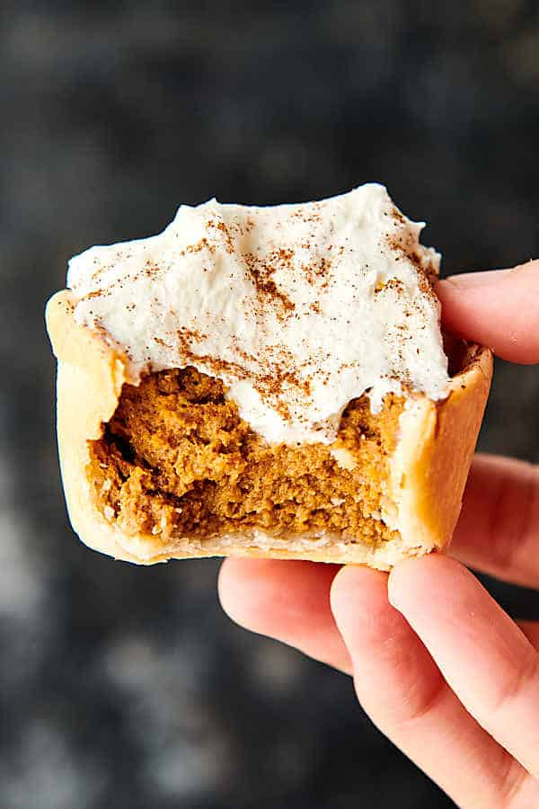 mini pumpkin pie with bite out held