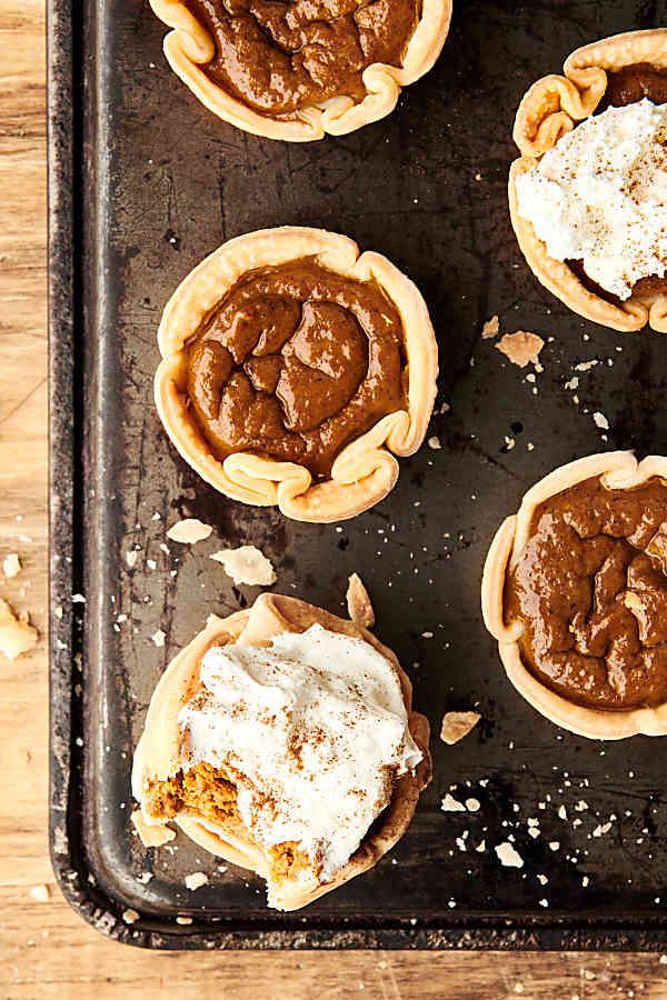 mini pumpkin pies on baking sheet above
