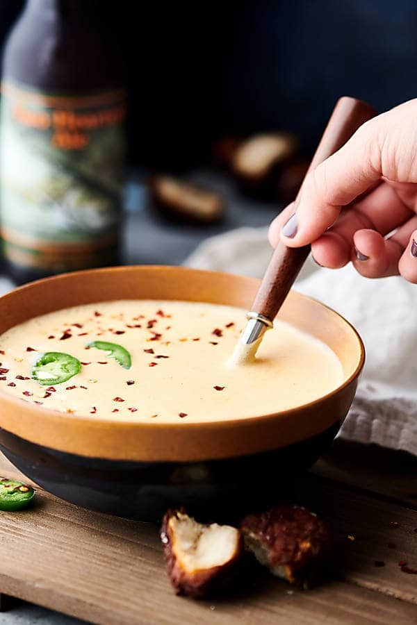 Spoonful being taken out of bowl of soup with pretzel bites sitting in front and bottle of beer in the background