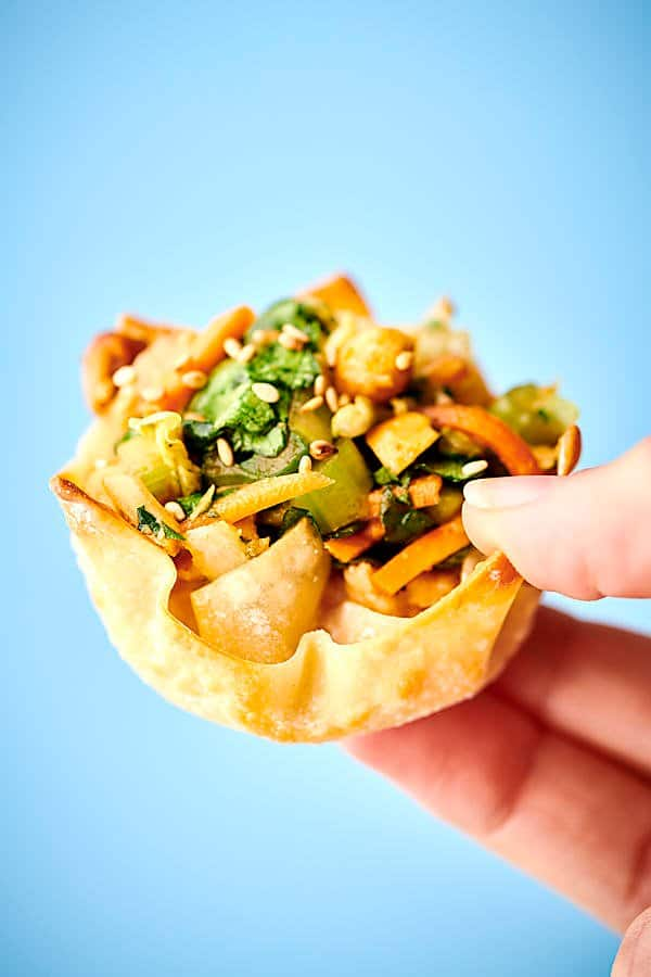 chinese chicken salad wonton cup held blue background