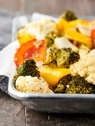 Only 10 ingredients and 30 minutes necessary for this Easy Roasted Vegetables Recipe! Cauliflower, broccoli, onion, peppers, garlic, oil, apple cider vinegar, salt and pepper! Don't like some of those veggies? Just swap them out for your favorites! Only 115 calories. Vegan. Gluten Free.showmetheyummy.com #roastedvegetables #vegan #glutenfree #healthy #recipe