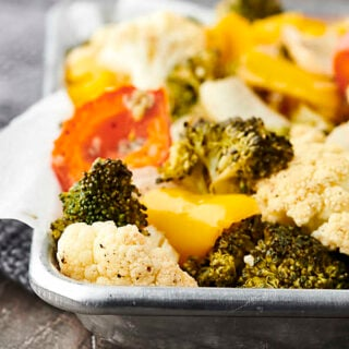 Only 10 ingredients and 30 minutes necessary for this Easy Roasted Vegetables Recipe! Cauliflower, broccoli, onion, peppers, garlic, oil, apple cider vinegar, salt and pepper! Don't like some of those veggies? Just swap them out for your favorites! Only 115 calories. Vegan. Gluten Free. showmetheyummy.com #roastedvegetables #vegan #glutenfree #healthy #recipe