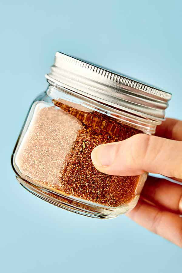 jar of homemade taco seasoning held blue background