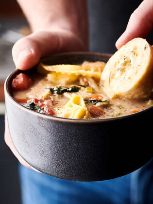 Chicken Tortellini Soup. An easy, cozy soup loaded with onions, carrots, celery, garlic, Italian seasoning, chicken broth, milk, fat free half-and-half (or heavy cream), a touch of white wine, store-bought rotisserie chicken, tomatoes, spinach, cheese tortellini, and parmesan cheese! Only 233 calories per cup! showmetheyummy.com #chicken #tortellini #soup #healthy #spinach