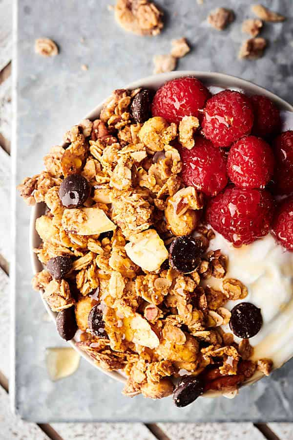 bowl of almond butter granola with raspberries and yogurt above