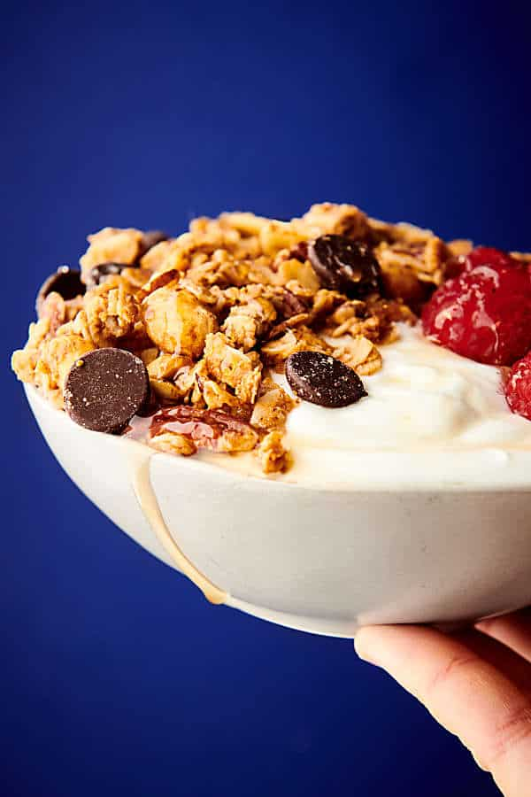 bowl of almond butter granola held blue background