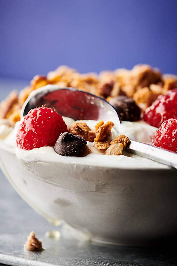 spoon in parfait bowl with almond butter granola