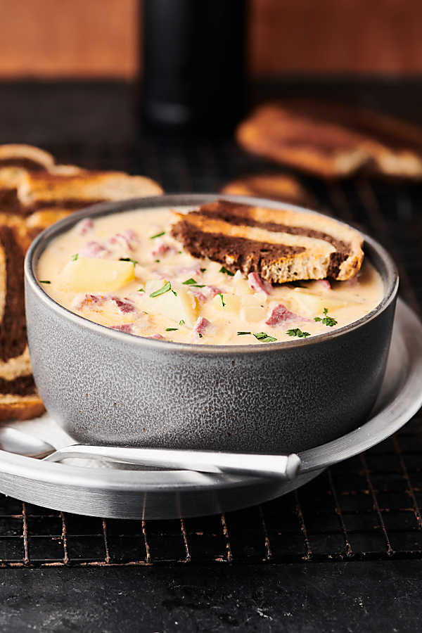 This Easy Reuben Soup Recipe only requires 12 ingredients! It's loaded with celery, onions, garlic, a touch of butter and flour, chicken broth, fat free half-and-half, Russian dressing, Yukon gold potatoes, sauerkraut, corned beef, and swiss cheese (plus salt and pepper). Served with toasted marbled rye bread! showmetheyummy.com #reuben #soup