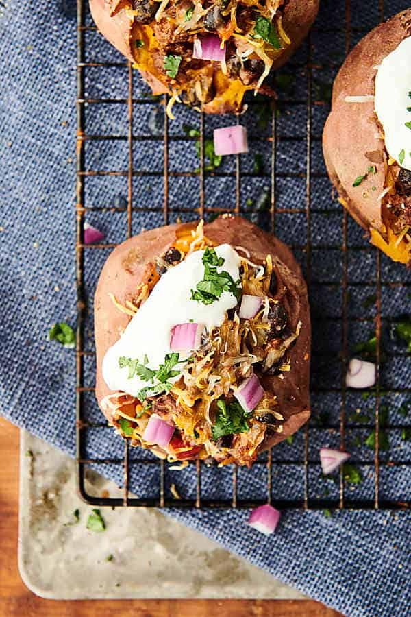 Healthy Taco Stuffed Sweet Potatoes. Tender sweet potatoes topped with homemade taco meat, peppers, onions, black beans, and optional toppings: cheese, cilantro, sour cream, greek yogurt, tortilla chips, pico de gallo, salsa, etc! showmetheyummy.com #healthy #sweetpotato #taco #beef
