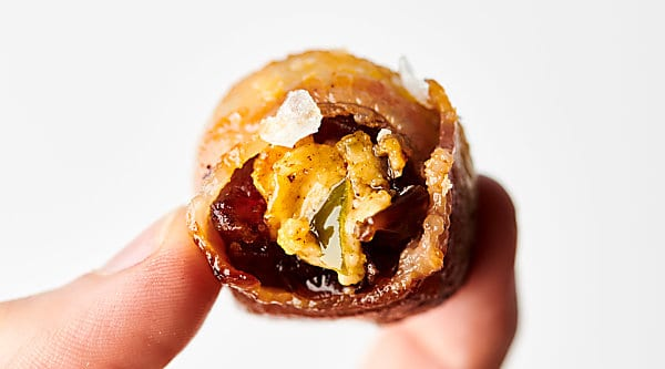 Jalapeno Popper Stuffed Dates. Sweet, chewy medjool dates stuffed with a quick and easy cream cheese jalapeno popper filling, and wrapped in bacon . . . these bite sized treats are the perfect combination of sweet, spicy, and savory! showmetheyummy.com #jalapenopopper #jalapeno #dates #creamcheese #bacon