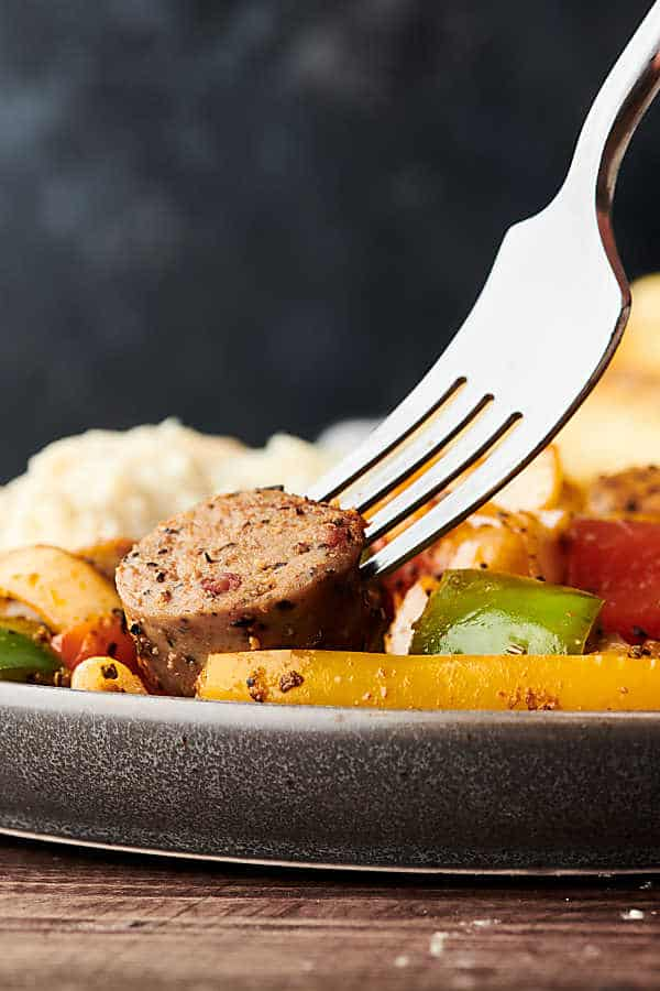 fork in piece of chicken sausage with peppers on plate