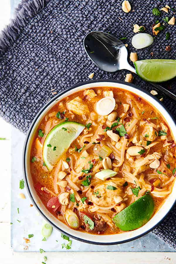 bowl of coconut curry chicken noodle soup with lime wedges above