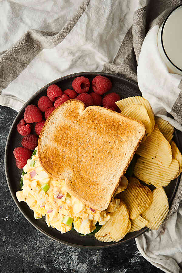 egg salad sandwich on plate with chips and raspberries above