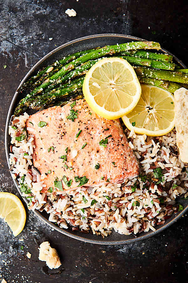 easy lemon honey baked salmon on plate with rice, lemon slices, and asparagus above