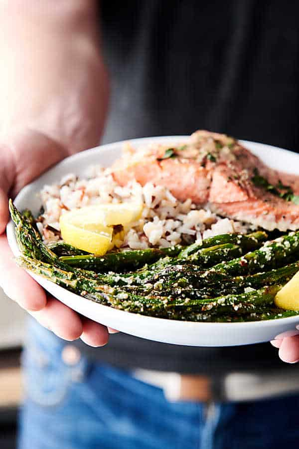 plate with salmon, rice, and asparagus held two hands