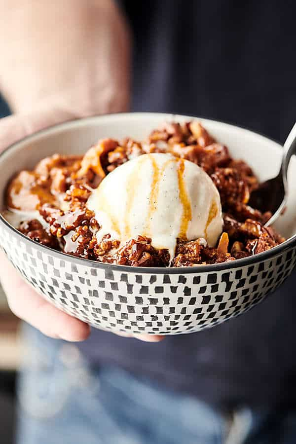 Easy Slow Cooker Carrot Cake Recipe. A layer of instant pudding is topped with pecans, coconut, and carrots, drizzled in caramel sauce, sprinkled with spice cake mix, and then topped with a butter, brown sugar, pecan streusel topping. Quick, easy, and SO decadent. The perfect gooey, fluffy crockpot cake! showmetheyummy.com #slowcooker #crockpot #cake #carrotcake #dessert