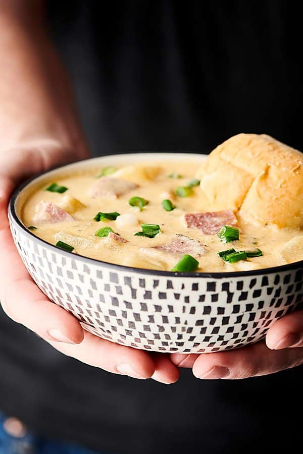 Ham and cheese potato soup in bowl held with two hands