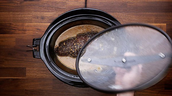 lid being taken off crockpot with ham in it