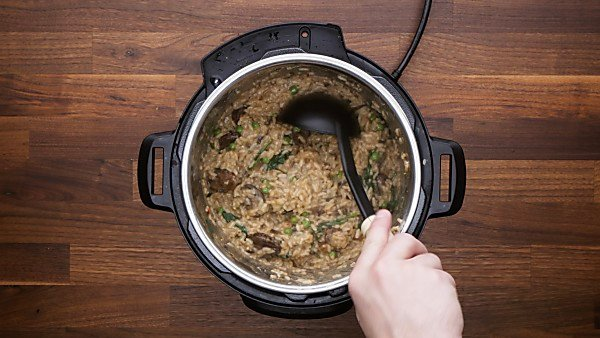 Mushroom risotto being scooped out of instant pot